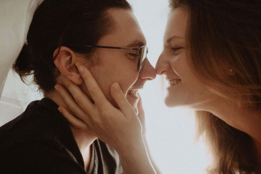 Adorable couple under blankets in romantic artsy couple photo session