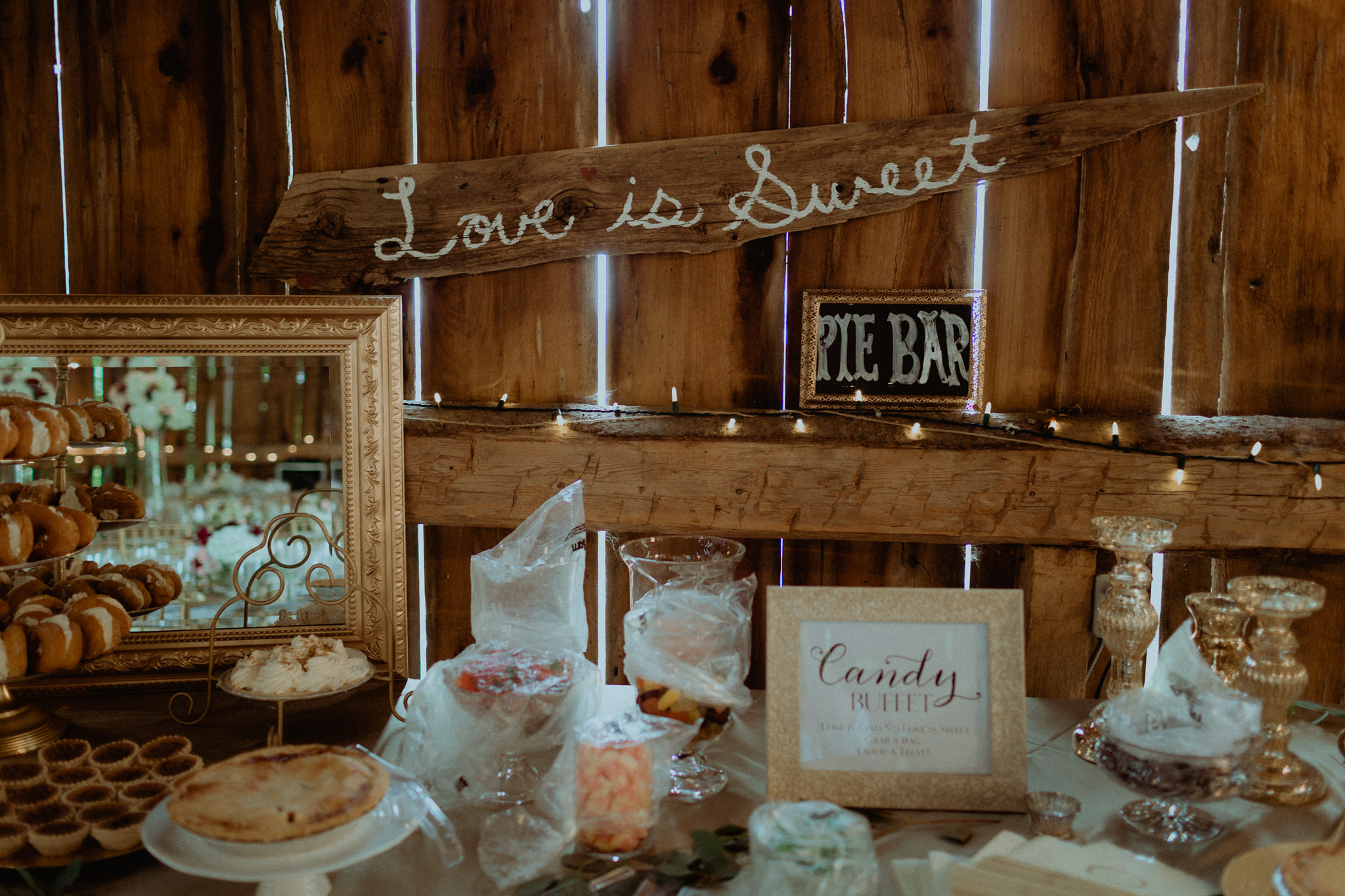 Love is sweet sign at candy bar in century barn wedding venue reception space