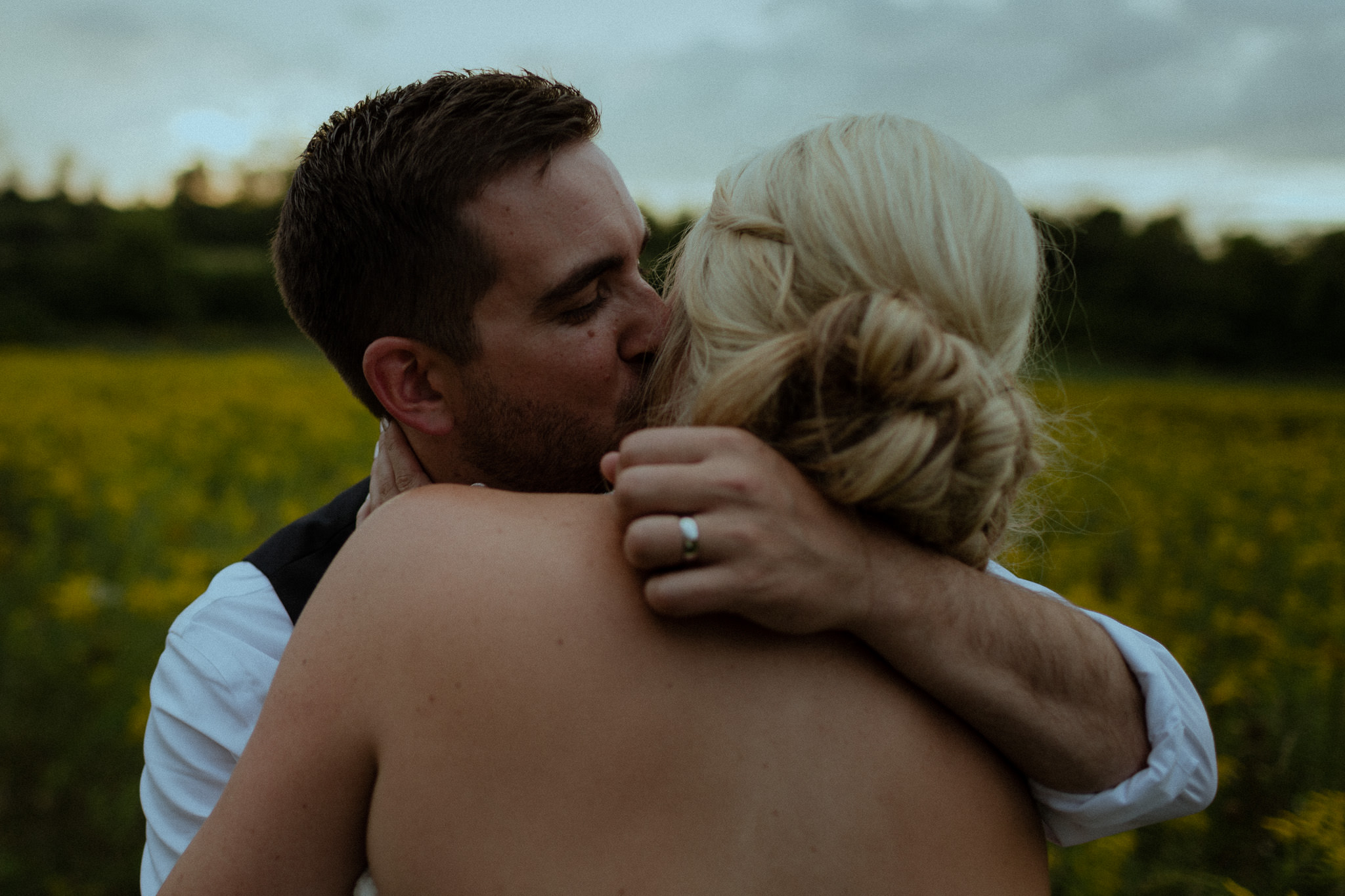 groom embracing his wife during sunset portrait session